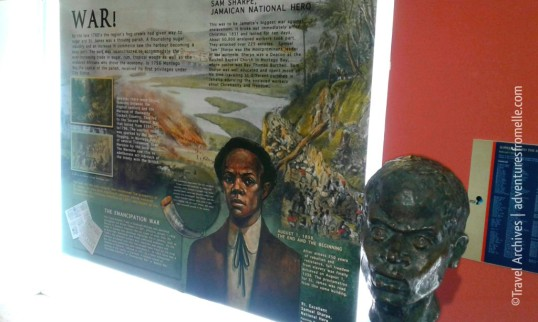 A poster about Sam Sharpe next to his bust