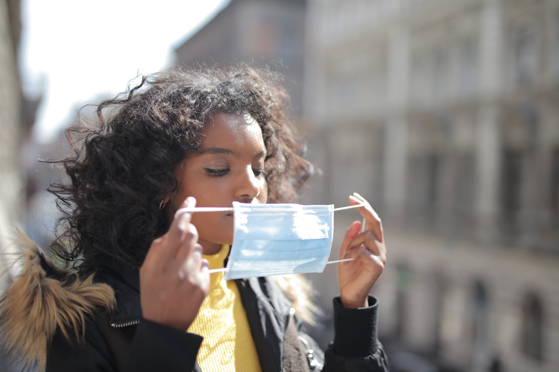 serious young ethnic lady putting on medical mask on street