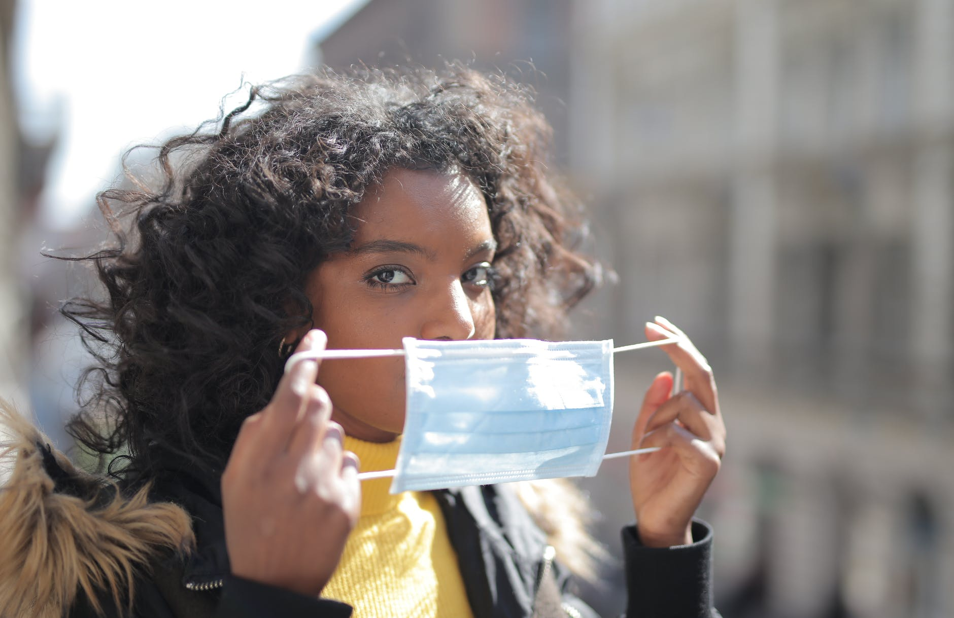 focused young ethnic lady putting on medical mask on street